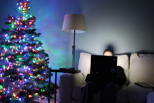 medium_11184349836 Cut Back Christmas Excess: Photo of man on Internet next to Christmas tree