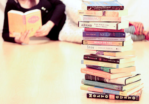 medium_7019888809 Reading Books Boosts Mood: Photo of woman lying on the floor reading next to a stack of books